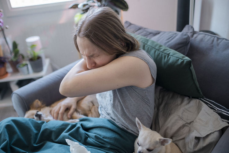 Midsection of woman sitting on bed at home