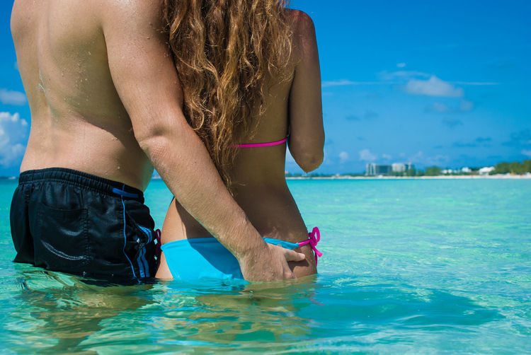 Midsection of couple standing in sea against sky