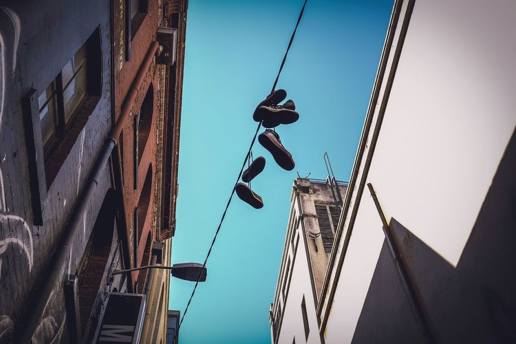 Low angle view of shoes hanging on cable by building against clear blue sky