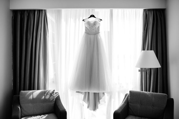 Front view of wedding dress hanging against curtain