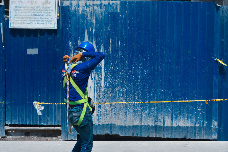 Man working on blue wall
