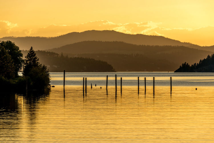 High angle view of wooden posts in river against silhouette mountains