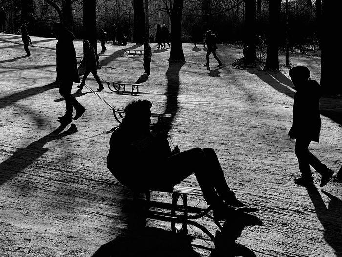Silhouette people on street in park