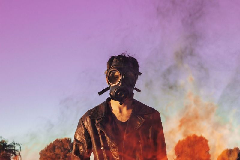 Man wearing gas mask while standing against sky during sunset