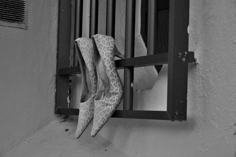 High heels hanging on window
