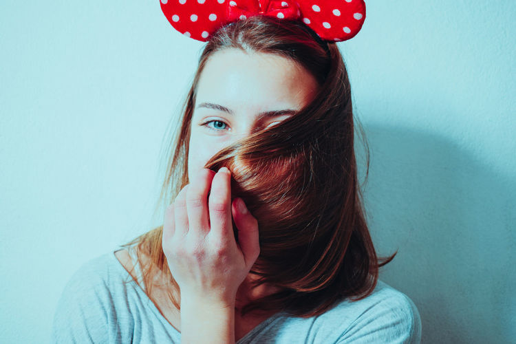 Close-up portrait of young woman with brown hair by wall