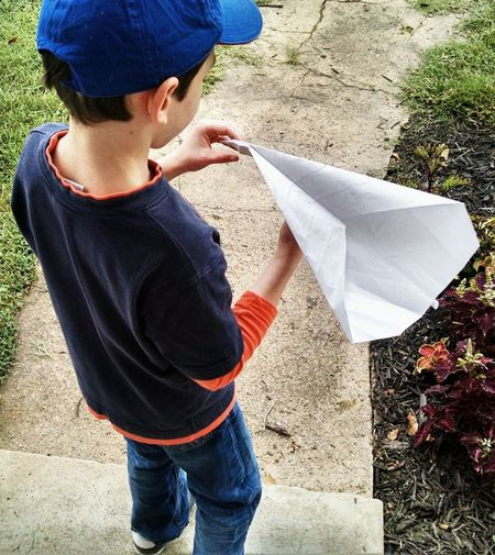 High angle view of boy playing with paper airplane