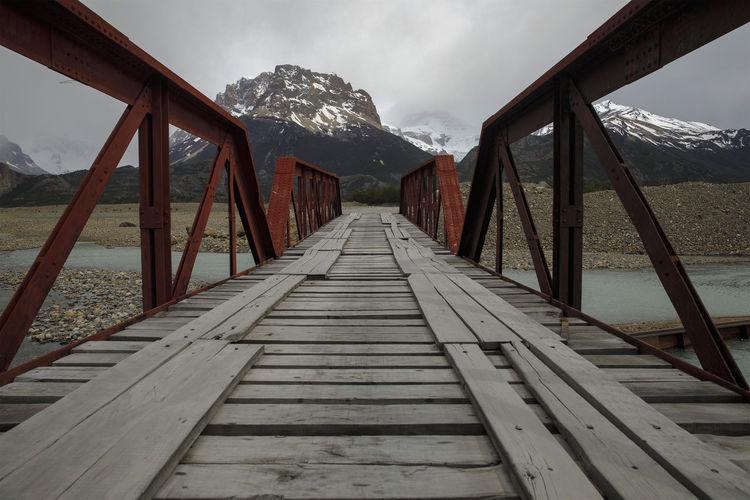 Footbridge leading towards snowcapped mountains against sky