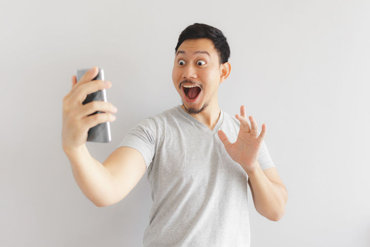 Portrait of happy man holding smart phone against white background