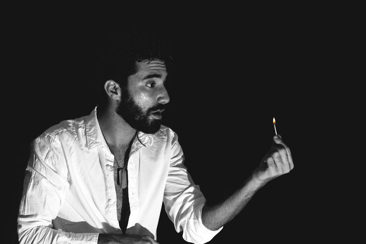 Young man holding matchstick against black background
