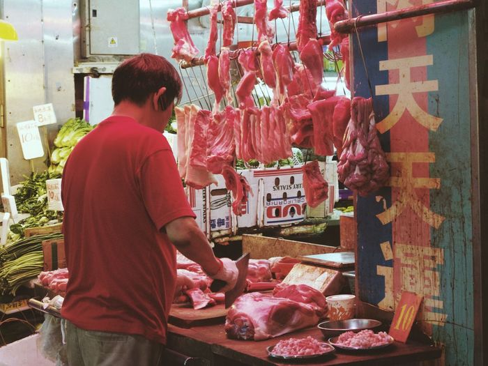 Rear View Of Butcher Cutting Meat At Market