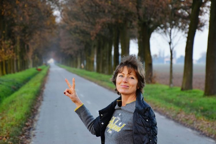 Portrait Of Mature Woman Gesturing Peace Sign On Road Amidst Trees