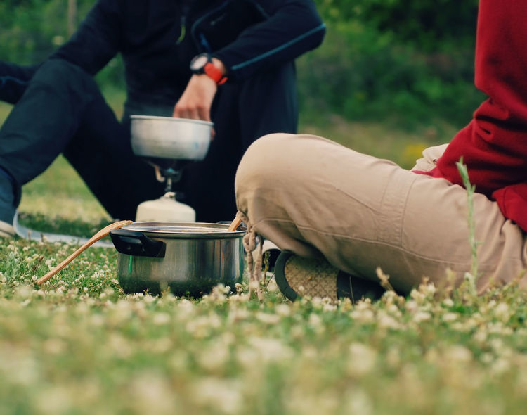 Lower part of a man and a woman cooking food in a saucepen on a portable camping gas stove in a green field Backpacking Camping Campinglife Casual Cooking Countryside Couple Field Food Friends Gas Stove Gas Stove Burner Grass Hiking Holiday Lower Angle Meal Mountain Outdoors Picnic Pot Relaxing Spring Summer Camp