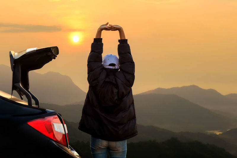 Rear view of man on car against mountains during sunset