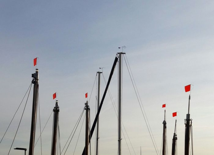 Low angle view of sailing masts against clear sky