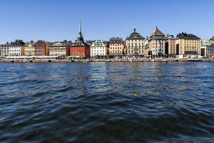 River by buildings against clear blue sky at strandvagen