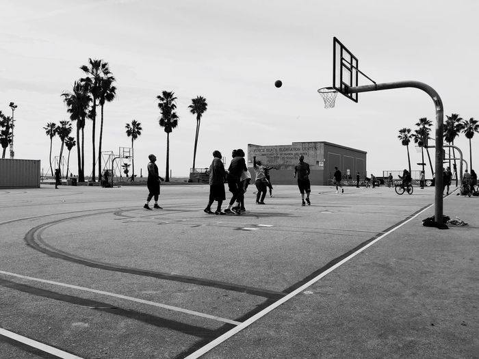 Friends playing basket ball at court against clear sky