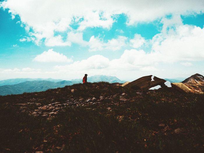 Man on mountain against cloudy sky