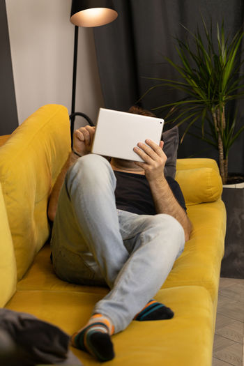 Midsection of man using mobile phone while sitting on sofa at home