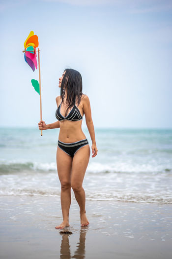 Beach Sea Water Land Sky One Person Horizon Over Water Swimwear Horizon Leisure Activity Clothing Holding Real People Beauty In Nature Standing Young Adult Bikini Scenics - Nature Nature Outdoors Beautiful Woman