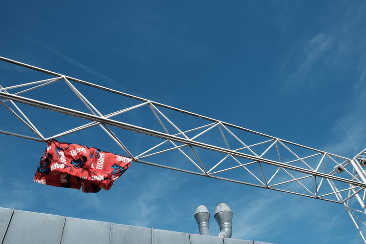 Low angle view of shorts hanging from metal against blue sky