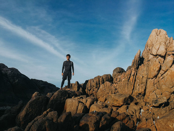 Low angle view of man standing on rock formation against sky