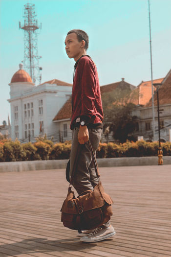 Full length of boy holding umbrella against sky in city