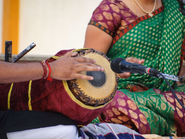 Midsection of man playing musical instrument by woman