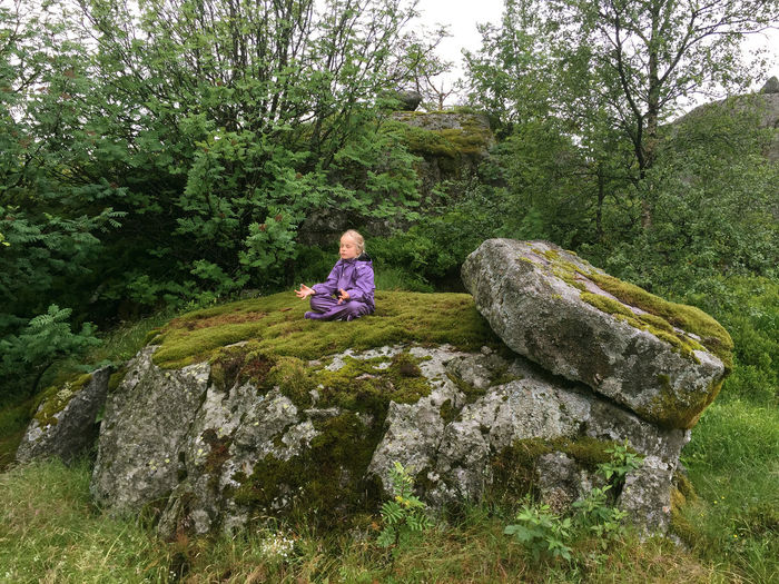 Girl doing yoga while sitting on rock at forest