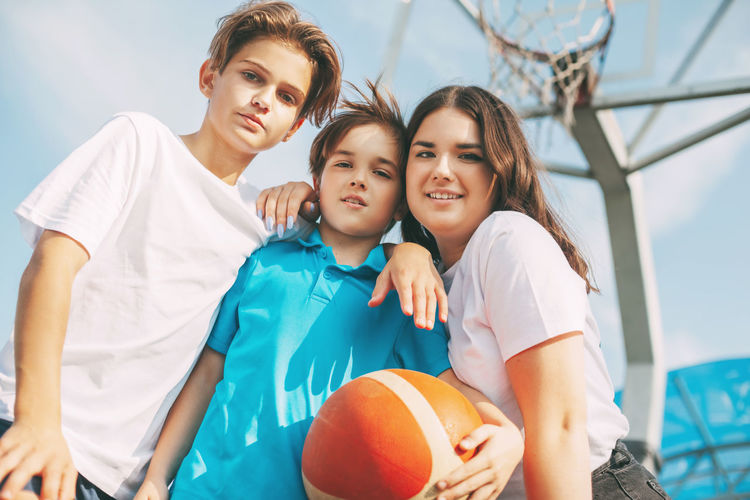 Portrait of smiling siblings with basketball standing against sky