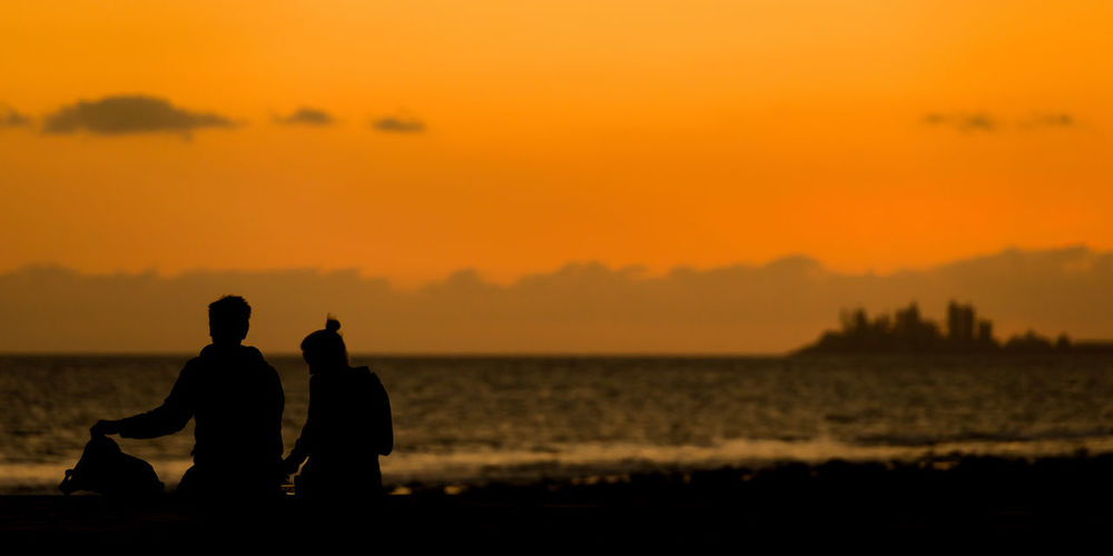 Silhouette Couple Sitting At Beach Against Orange Sky