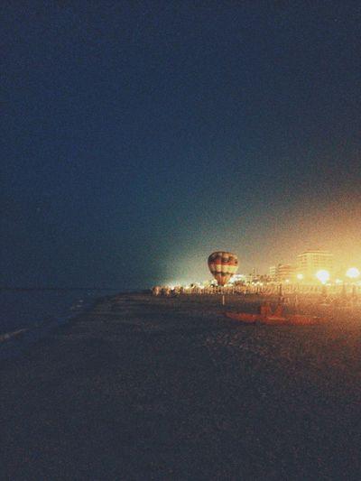 Illuminated street light on beach against sky at night