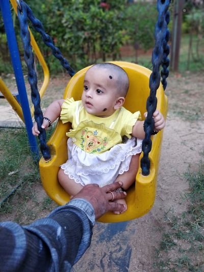 Cropped Hand Of Man Touching Girl Legs Sitting On Swing
