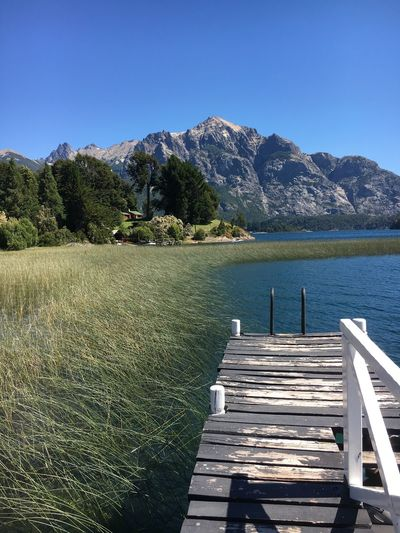 Tranquil Scene Nature Clear Sky Mountain Scenics Beauty In Nature Tranquility Water Day Lake Pier Idyllic Outdoors No People Wood - Material Blue Landscape Sky Mountain Range Grass dock