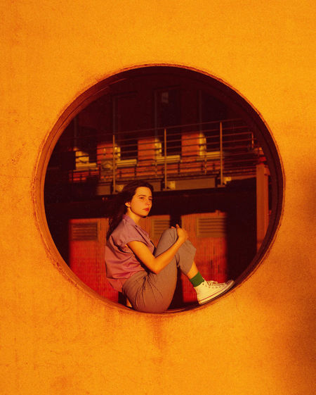 Woman sitting in mirror against wall