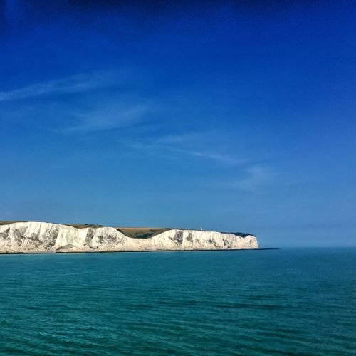 White cliffs of dover by sea against blue sky
