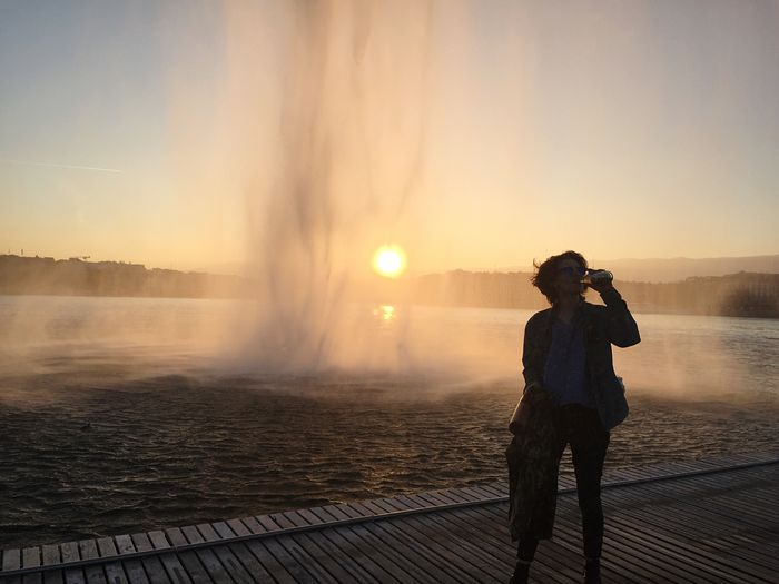Woman having drink while standing on pier by lake geneva with fountain against sky during sunset