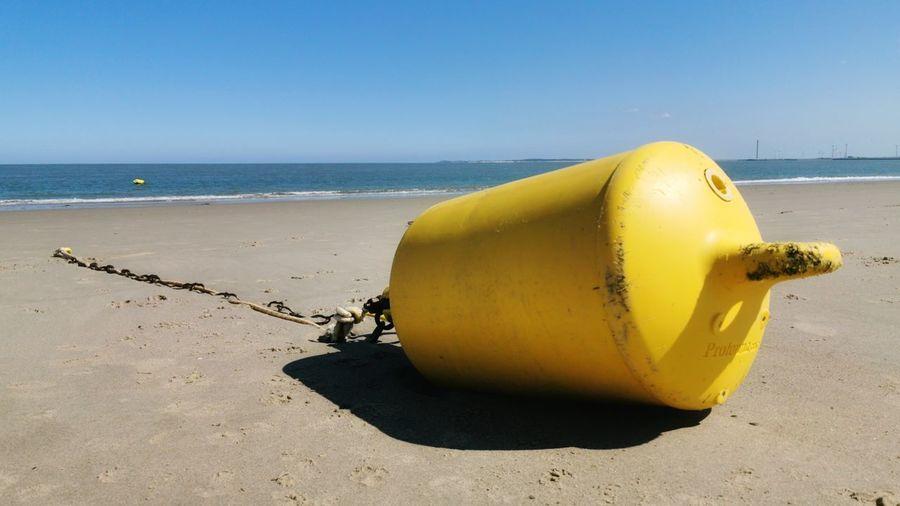 Yellow umbrella on beach against clear sky