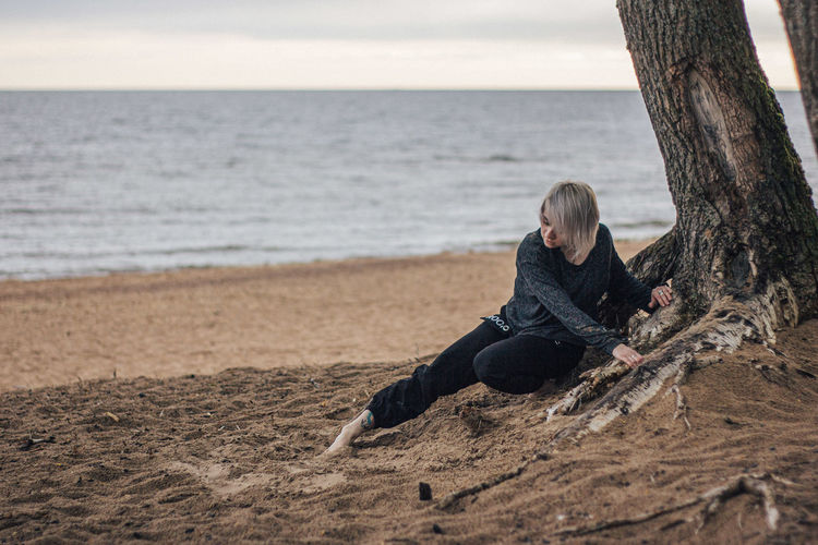 Man sitting on tree trunk at beach against sky