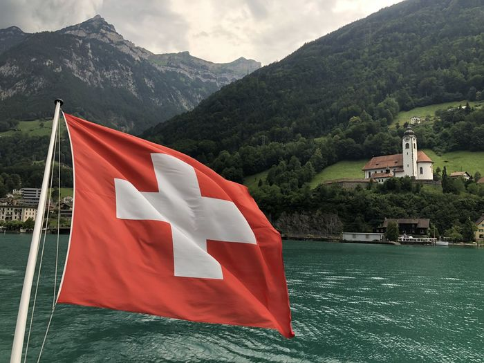 Scenic view of flag by lake against mountains