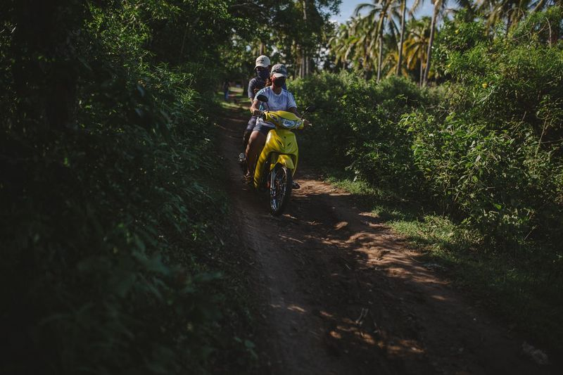 People riding motorcycle on dirt road