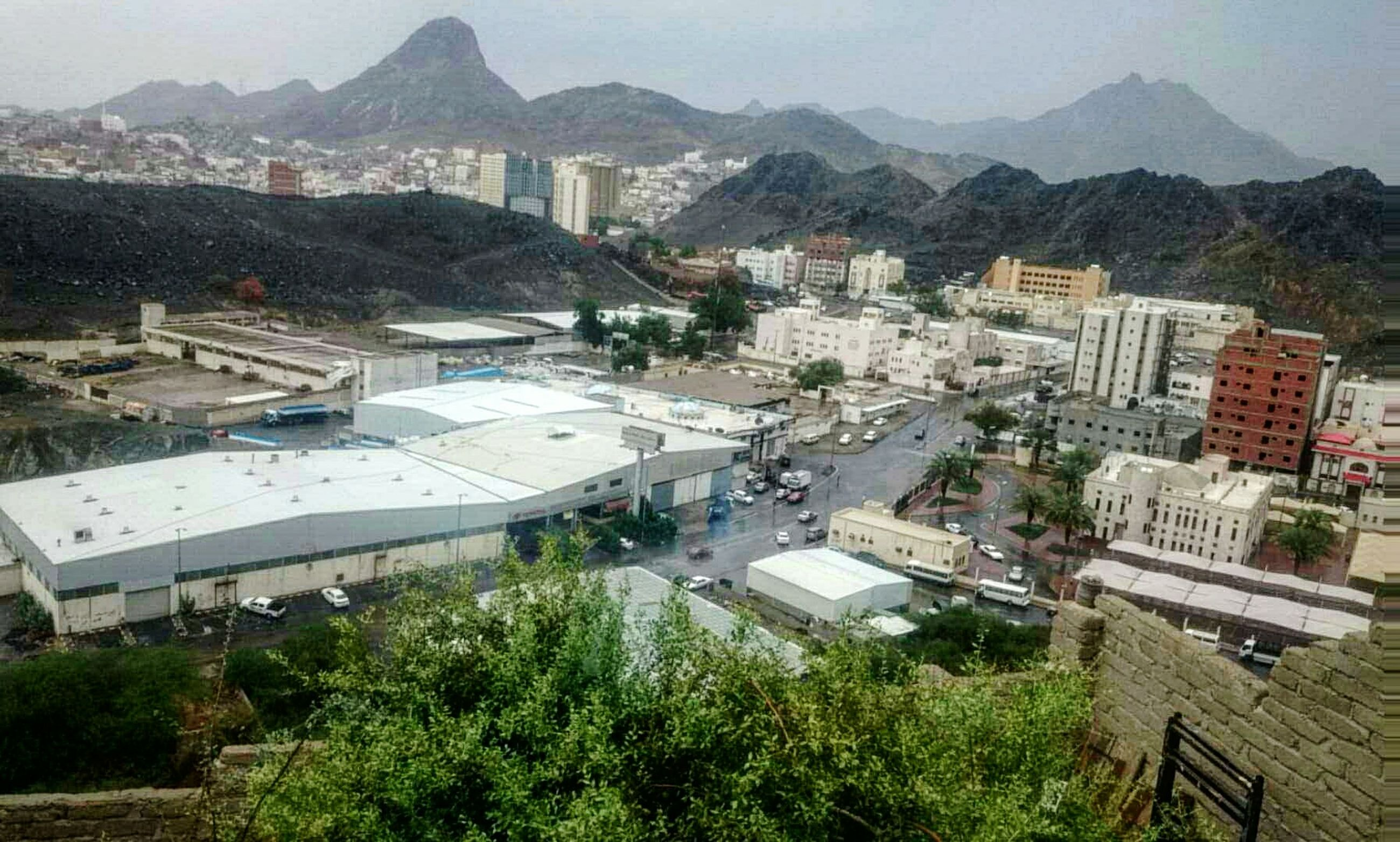 building exterior, architecture, built structure, mountain, high angle view, cityscape, city, residential district, tree, residential building, crowded, residential structure, mountain range, house, town, townscape, landscape, community, human settlement, sky