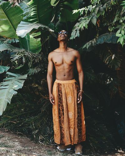 Full length of shirtless man standing against tree