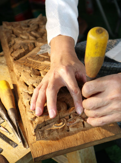 Cropped hands of craftsperson carving wood in carpentry workshop