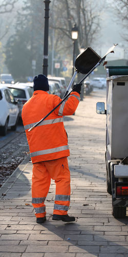 sweeper with an orange jacket collecting rubbish along the streets of a big city Cleaning Cleaning Equipment NettUrbino Rubbish Adult Day Manual Worker Occupation One Person Outdoors People Protective Workwear Rear View Sweeper Sweeper Road Sweepers Transportation Warm Clothing Waste Management Working