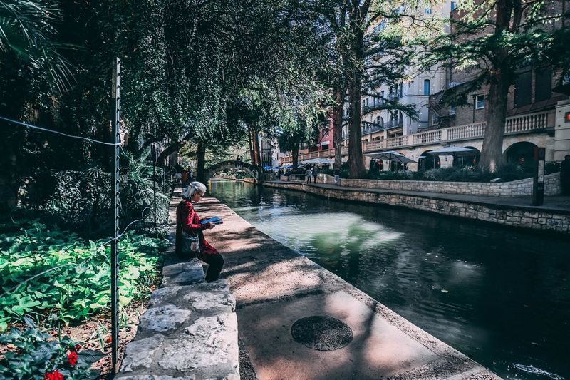 Man standing on footbridge over river in city