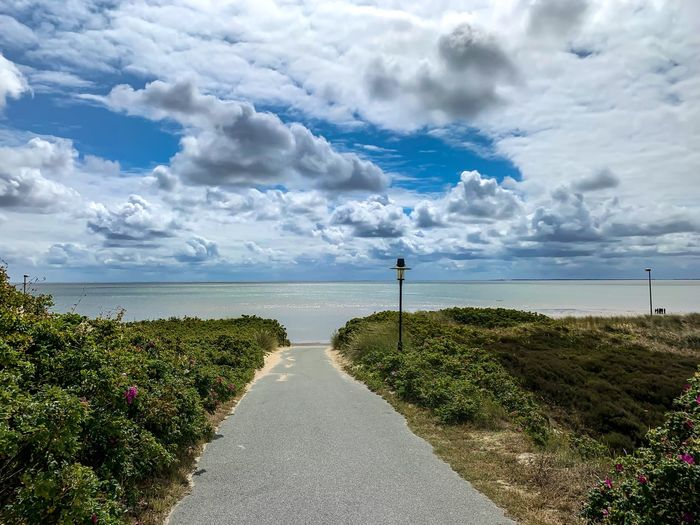 Scenic view of road by sea against sky