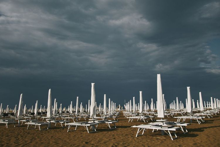 Beach umbrellas against cloudy sky