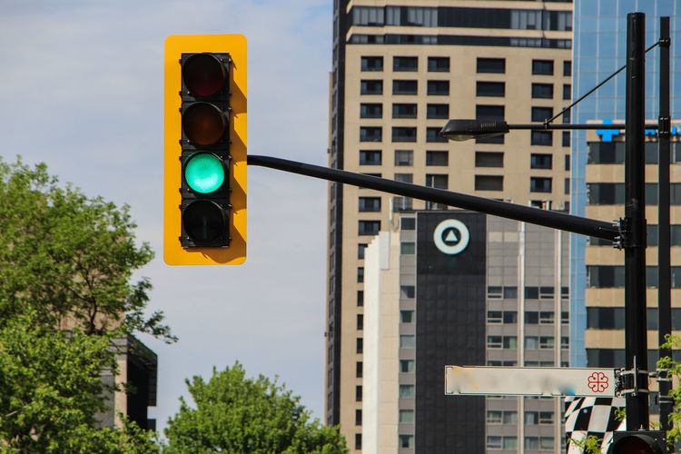 Architecture Blue Building Built Structure City City Life Day Directional Sign Information Information Sign Low Angle View Modern No People Office Building Outdoors Pole Road Sign Sky Stoplight Tall - High Traffic Light  Tree Montréal The Color Of Technology