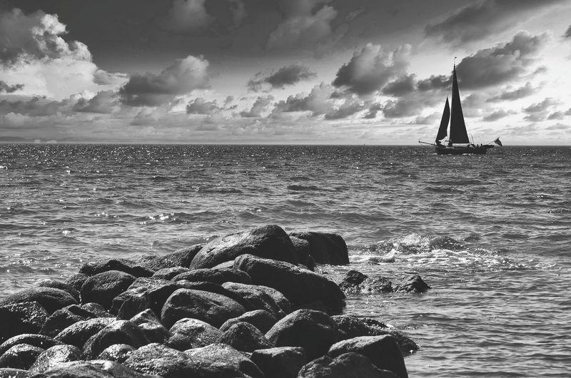 Sailboats on rocks by sea against sky